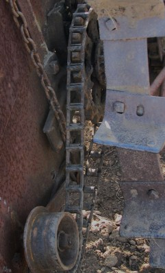 The driving chain on the gear with the large ground wheel with the spades on the rim to keep it from slipping.  The other chain in the photo at the left going up is holding the tensioner wheel tight against the drive chain.