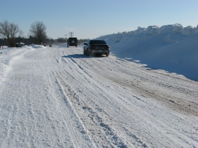 Green's Road and cars lend scale to the sizeable snow banks thrown up by the County plows.