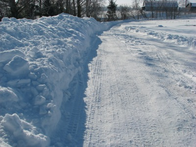 More high thrown snow banks, thrown leeward side to keep fill in down somewhat. Driveway is now nice and smooth anyway.