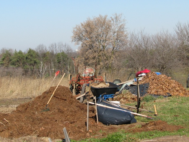 Piles of well broken down hay mulch, piles of leaves and various tools lying about.
