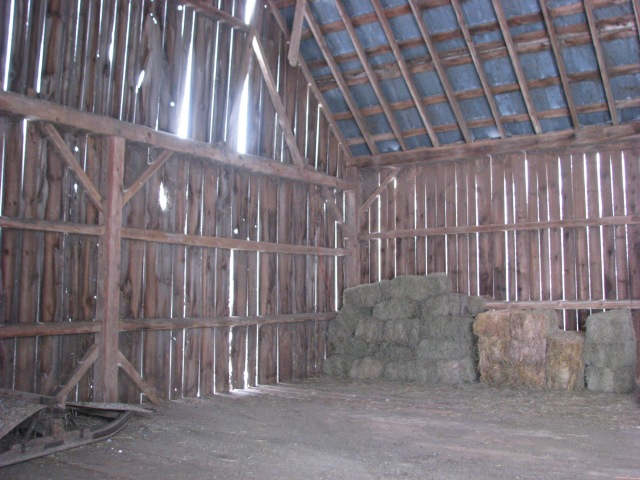 The east bay of our barn loft.  quite empty except for a small number of small square hay bales